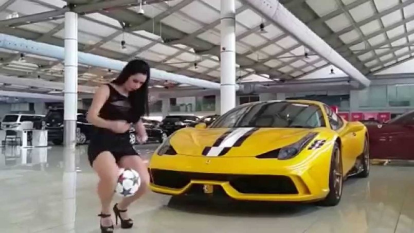 Model Raquel Benetti Juggles Soccer Ball Next To Ferrari