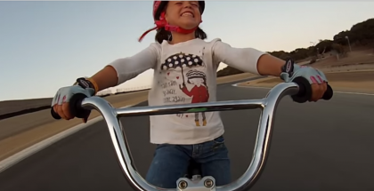 Girl Rides Bicycle Down Laguna Seca
