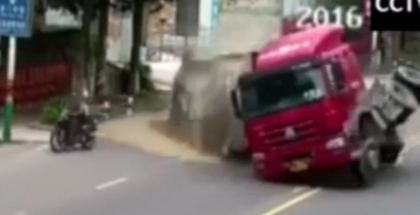 Truck full of sand almost flips over onto of a motorcyclist (1)